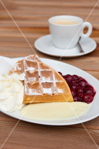 A Belgian waffle with cream, cherries and vanilla sauce