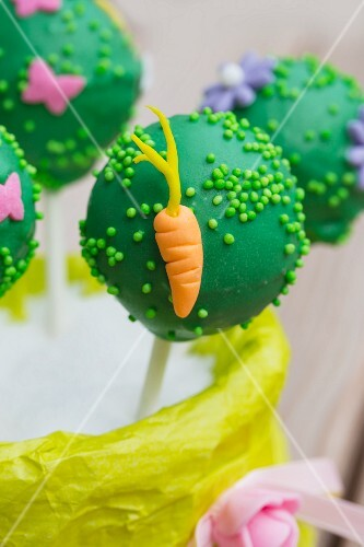 A green cake pop decorated with a carrot