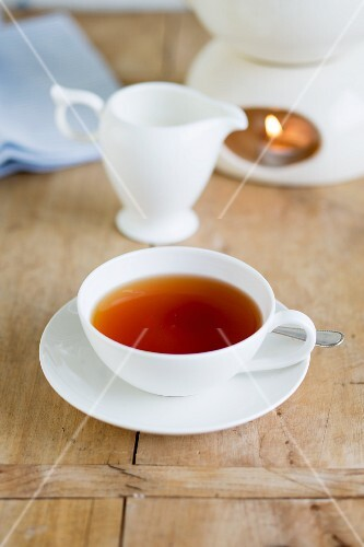 A cup of tea, a jug of milk and a teapot warmer on a wooden table