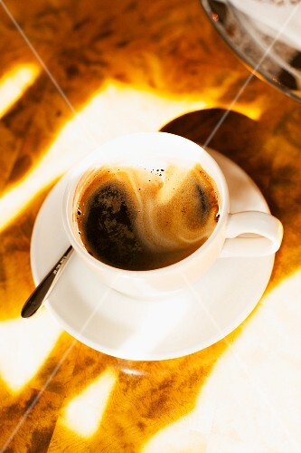 A cup of black coffee in the sunshine