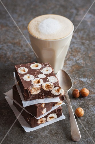 Chocolate slices with hazelnuts and a caffe latte