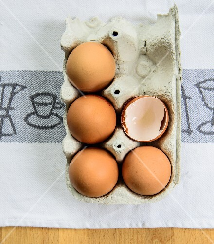 Whole eggs and egg shells in an egg box