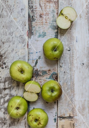 Green cooking apples, whole and halved, on a weathered wooden surface