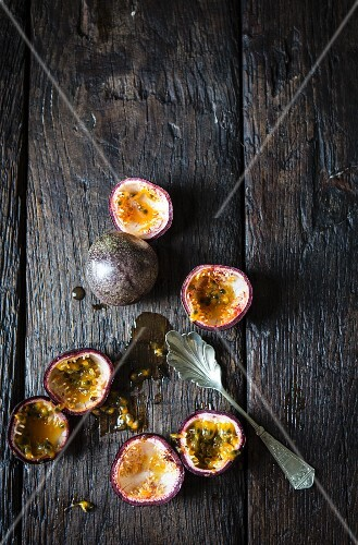 Whole and hollowed out passion fruits on a wooden surface