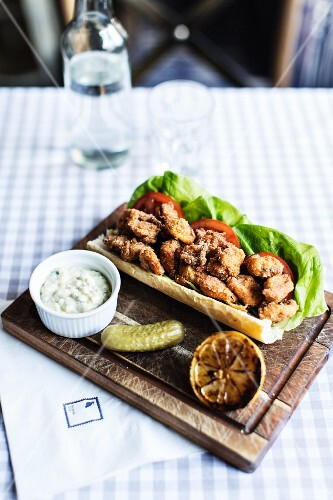 Po boy (fried oysters in a baguette with tartar sauce, gherkin and grilled lemon)