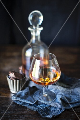 Brandy in a glass and the carafe with chocolate pralines