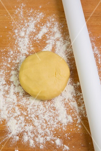 Shortcrust pastry and a rolling pin on a floured work surface