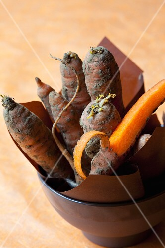 Organic carrots covered in soil, one peeled