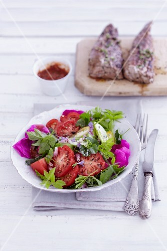 A wild herb salad with tomatoes and rose petals