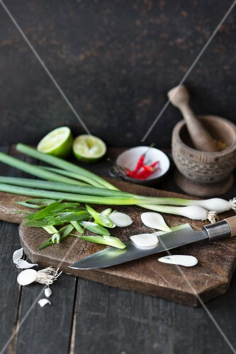 Sliced spring onions on a chopping board with a mortar, chillis and limes in the background