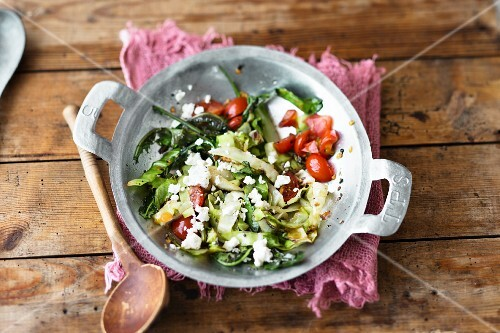 Stir-fried pointed cabbage with tomatoes and sheep's cheese