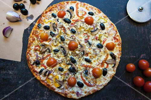 Pizza topped with cherry tomatoes, mushrooms, onions and olives