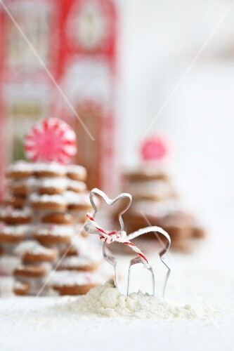 A cookie cutter in front of gingerbread biscuit trees decorated with icing sugar and peppermint bonbons