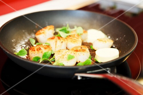 Scallops with field thyme, sea salt and butter being fried in a pan
