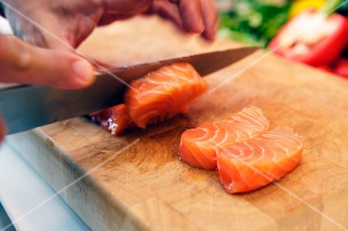 Raw salmon being sliced