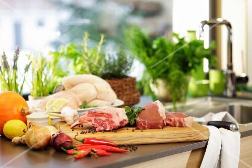 Pork, vegetables, chicken and herbs in a kitchen