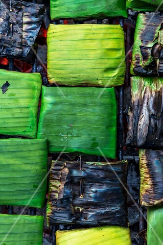 Banana leaf parcels filled with fish on a barbecue