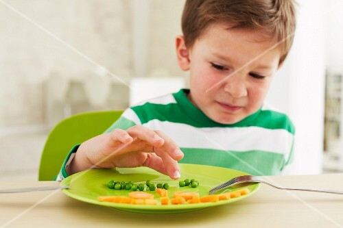 A little boy who doesn't want to eat peas and carrots
