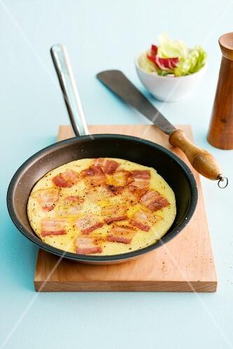 A bacon pancake in a non-stick pan