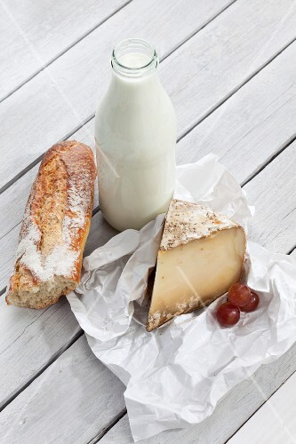 An arrangement featuring a bottle of milk, sheep's cheese and a baguette
