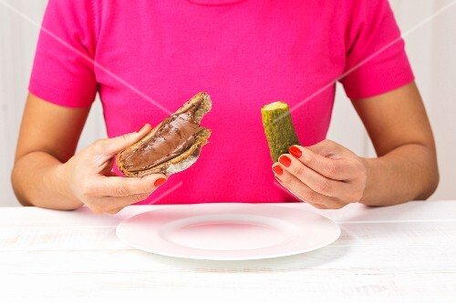 A woman eating a gherkin and a chocolate spread sandwich