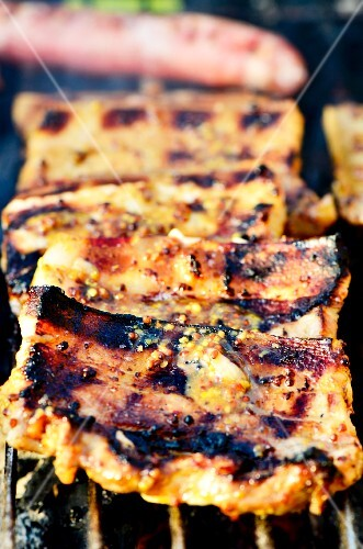 Pork belly marinated in a honey and mustard marinade on a barbecue