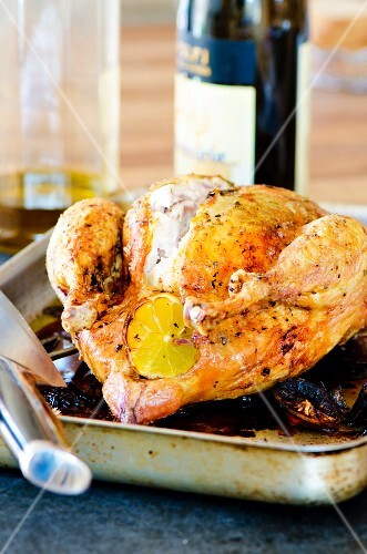Roast chicken with lemons in a roasting tin