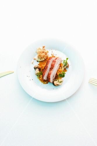 Roast free range pork on a vegetable salad with mushrooms