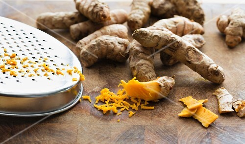Fresh turmeric roots with a grater