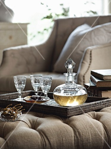 Glass carafe and cut crystal glasses on wicker tray on ottoman in elegant ambiance