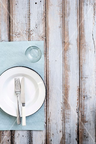 A plate with cutlery and a water glass on a wooden table