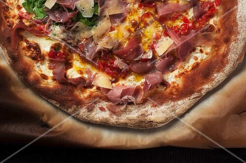 A ham pizza on a piece of baking paper (seen from above)