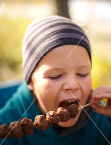 A child eating a meatball skewer at an autumn picnic