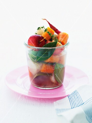 An arrangement of vegetables, apple and herbs in a glass