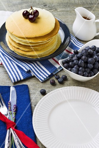 A table laid with a stack of pancakes and fresh blueberries