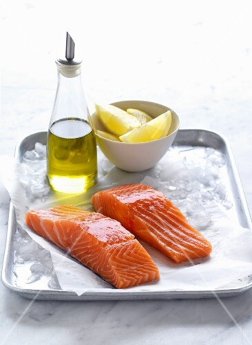 Salmon fillets on ice with olive oil and lemon wedges