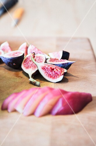 Fresh figs and red wine pears on a wooden board