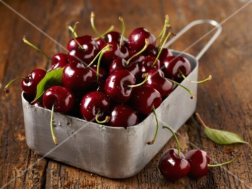 Freshly washed cherries in a metal container on a wooden surface