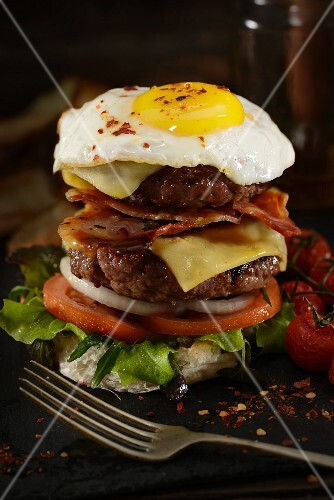 A cheese burger with bacon and a fried egg