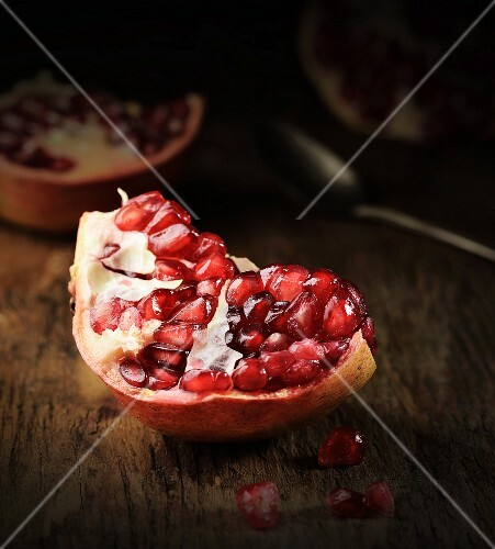 A piece of pomegranate on a wooden surface