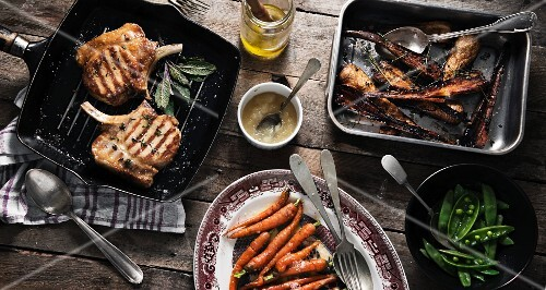 Grilled pork chops, roasted pistachios, carrots and mange tout