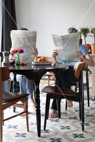 A couple reading newspapers at the breakfast table