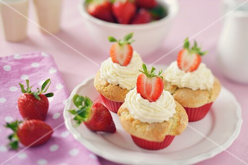 Strawberry muffins with a mascarpone topping on a white plate