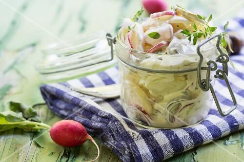 Kartoffelsalat mit Radieschen und Thymian in einem Einmachglas auf grünem Holztisch
