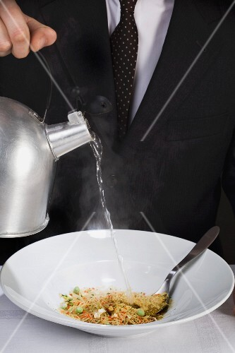 A man pouring water onto instant soup powder in a bowl