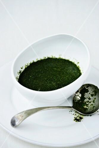 A bowl of mint sauce next to a sauce ladle