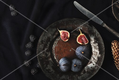 An arrangement of fresh figs and blackberries on an antique plate
