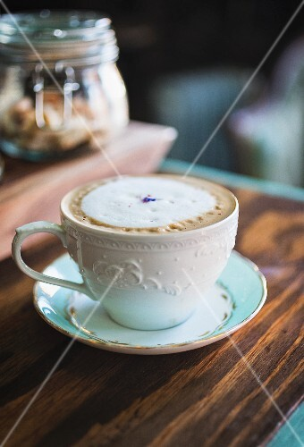Cafe latte with milk foam and a lavender flower