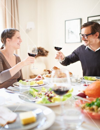 A couple raising a toast with glasses of red wine at a table laid for Thanksgiving