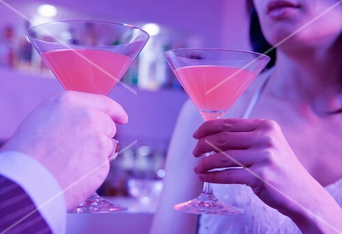 A man and a woman toasting with cocktails